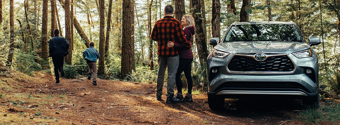 family standing in middle of forest with Toyota Highlander